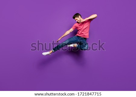 Full length photo of handsome attractive guy jump high up spread arms dance strange dab moves wear casual pink t-shirt jeans footwear isolated purple color background #1721847715