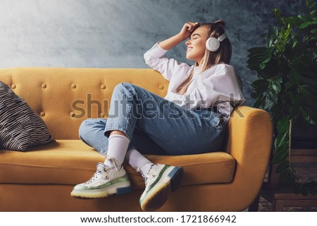 Beautiful blonde woman in white headphones sits on a yellow sofa and enjoys listening to music, podcast.