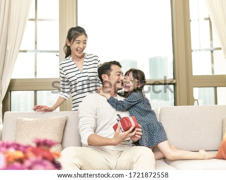 little asian girl hugging father after giving a present #1721872558
