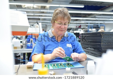 friendly woman working in a microelectronics manufacturing factory - component assembly and soldering  #1721889520
