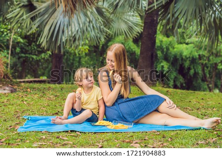 Coronavirus is over. Quarantine weakened. Take off the mask. Now you can go to public places. Mom and son had a picnic in the park. Eat healthy fruits - mango, pineapple and melon. Children eat #1721904883