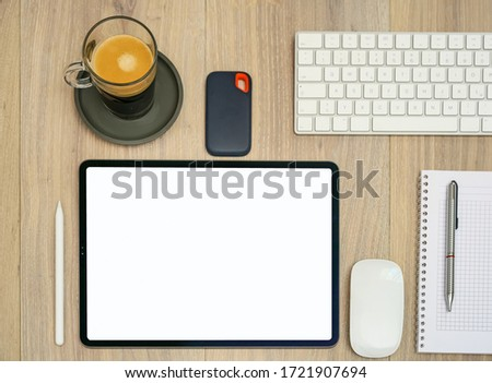 Modern tablet computer, pen, notebook, coffee cup, keyboard, mouse and external data storage device on office table. Home office. #1721907694