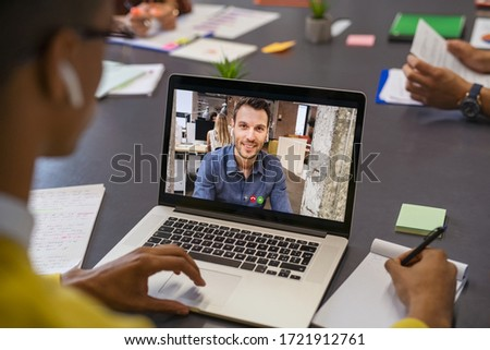 Business partners talking through video call. Back view of african businessman in office doing video chat calling a client. Young man and his business colleague talking to each other through a video. #1721912761