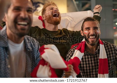 Three friends cheering for england sports team. Football fans wearing poland flag and scarf with painted face celebrating victory in bar. Group of young men shouting excitingly for soccer team. Royalty-Free Stock Photo #1721912767
