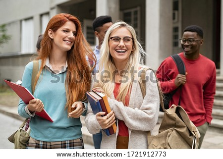 Multiethnic group of happy young women and men walking in college campus. Cheerful group of multiethnic friends feeling relaxed after university exam. Smiling classmates laughing and looking away. #1721912773