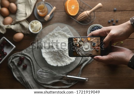 The top view of the hand take photo of ingredients and method bakery or dessert with the smartphone on the table. Tutorial food photography, A lifestyle to social media.Flat lay photography.
