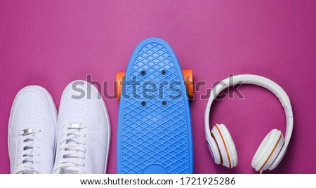 Hipster outfit. Skateboard with headphones and sneakers on purple background. Creative fashion minimalism. Trendy old fashionable style. Minimal summer fun. Music concept #1721925286