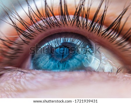 caucasian human blue eye in a contact lens looking up close up. contact lens vision medical correction concept Royalty-Free Stock Photo #1721939431