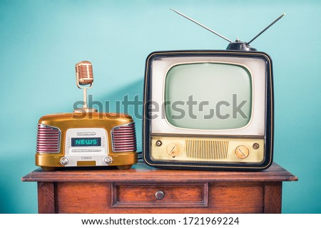 Retro outdated TV set from 60s, old FM radio, golden microphone on oak wooden table front mint blue background. News, press conference or nostalgic music concept. Vintage style filtered photo #1721969224