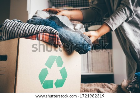 Recycle clothes concept. Recycling box full of clothes. Royalty-Free Stock Photo #1721982319