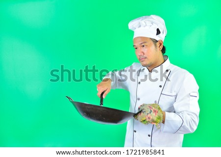 The chef uses a pan and spatula on over green screen background.