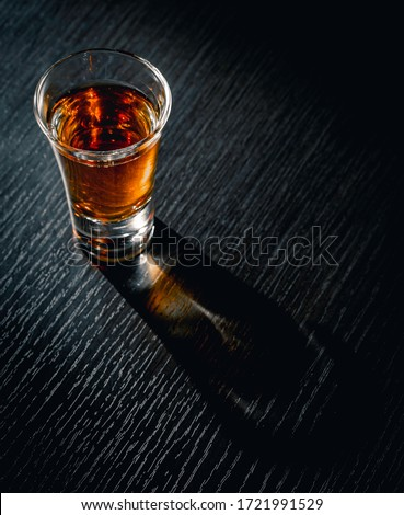 Alcoholic drink shot on a black wooden background
