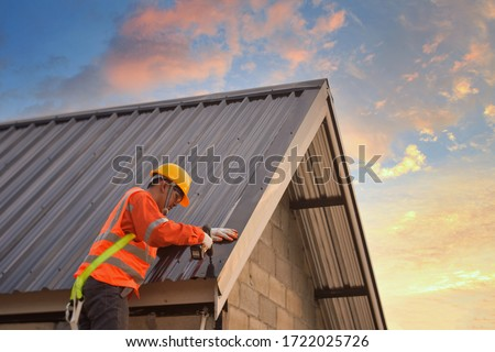 Roofer Construction worker install new roof,Roofing tools,Electric drill used on new roofs with Metal Sheet. Royalty-Free Stock Photo #1722025726
