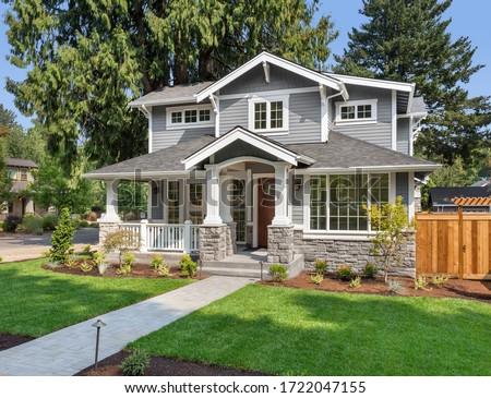 Beautiful new home exterior with covered porch and green grass on bright sunny day with blue sky #1722047155