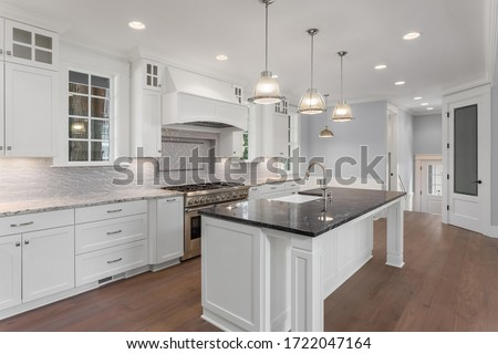 Beautiful kitchen in new luxury home with large island, hardwood floor, and pendant lights Royalty-Free Stock Photo #1722047164