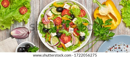 Greek salad with cucumeber, olives, feta cheese, cherry tomatoes, bell pepper and lettuce. Summer diet salad concept. Tasty greek salad in bowl on wood, top view, banner #1722056275