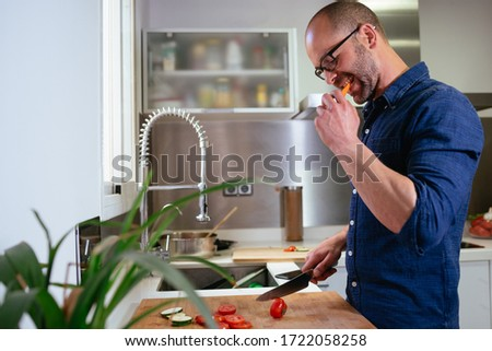 Side view of man with glasses eating vegetables in a modern kitchen while preparing a recipe. #1722058258