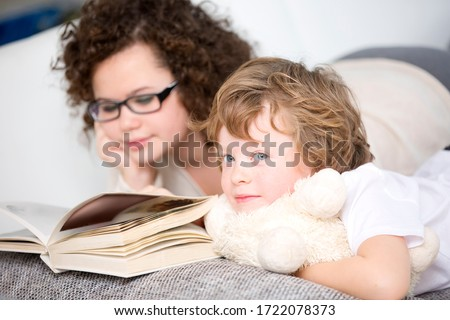 Boy relaxing on sofa with sister reading book #1722078373