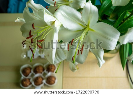 horizontal picture of a bunch of madonna lilies formed in a bouquet against background of wooden table at kitchen