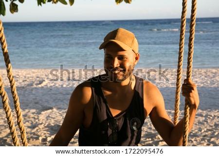 boy enjoying sunset on a swing on a beach in Philippine islands #1722095476