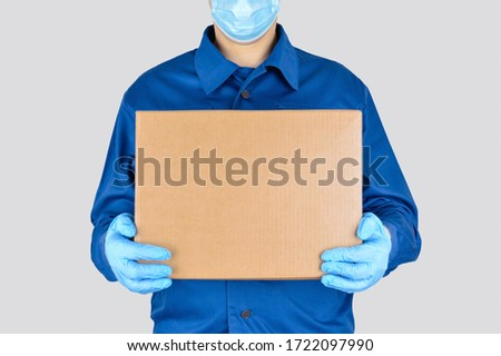Delivery man in uniform with box isolated on gray background. Medical supplies delivery.  #1722097990