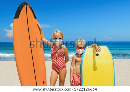 Young surfer kids with surf boards wear protective mask on sea beach. Cancelled cruises, tours due coronavirus COVID-19 epidemic. Travel ban for family vacation, tourism industry crisis at summer 2020 Royalty-Free Stock Photo #1722126664