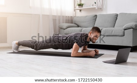 Online workout. Young man doing plank exercise with online tutorial at home, panorama, free space Royalty-Free Stock Photo #1722150430