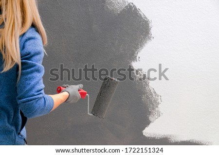 Girl holds a roller in hand close-up. Girl repaints the wall in gray. Repair in the room. DIY repair. #1722151324