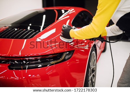 Car detailing - Worker with orbital polisher in auto repair shop. Selective focus. Royalty-Free Stock Photo #1722178303