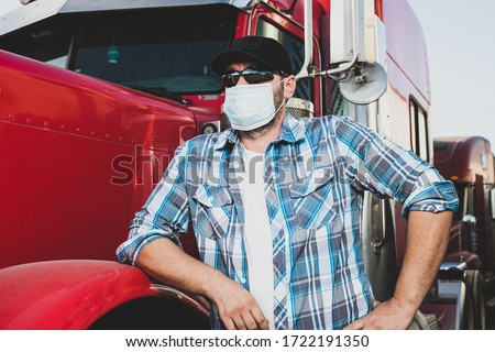 Semi truck professional driver on the job in casual clothing wears safety medical face mask. Confident looking trucker stands next to red big rig wearing protection sunglasses and surgical mask. #1722191350