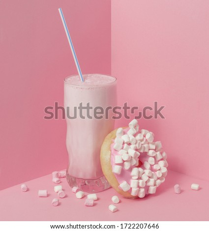 Milkshake with a straw and a donut with marshmallows on a pink background. Scattered white marshmallows. Glamorous and geometric picture