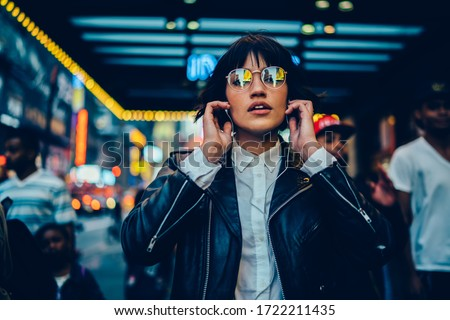 Half length portrait of trendy female millennial in electronic spectacles looking at camera during time for listening audio book and walk in metropolitan downtown, generation z in earphones Royalty-Free Stock Photo #1722211435