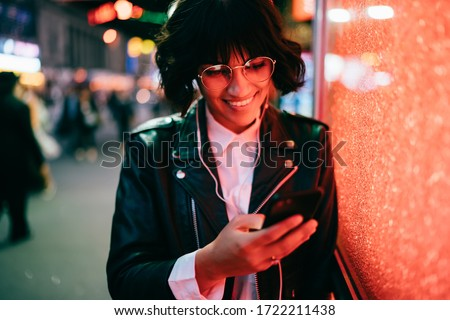 Happy hipster girl in optical spectacles checking shared video web content listening sounds in electronic headphones, trendy dressed blogger communicating with followers from website using smartphone #1722211438