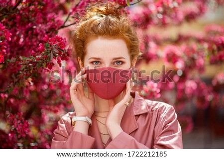 Redhead woman wearing trendy fashion pink monochrome outfit with luxury designer protective face mask. Close up portrait. Vogue, street style during quarantine of coronavirus outbreak.  #1722212185