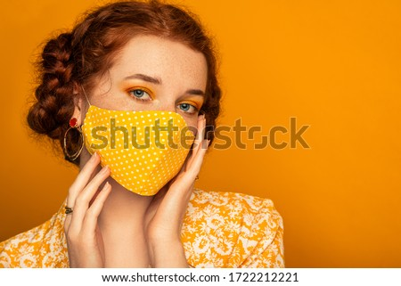 Woman wearing stylish handmade protective face mask posing on orange background.  Model with colorful eyes makeup. Fashion during quarantine of coronavirus outbreak. Copy, empty space for text #1722212221
