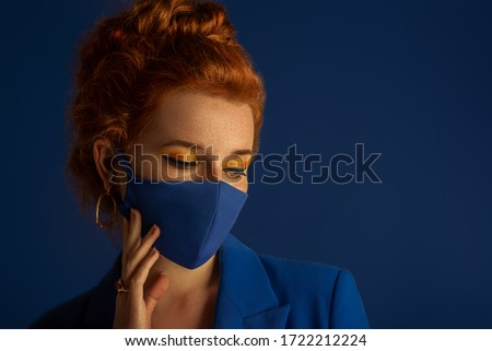 Redhead woman wearing trendy fashion blue monochrome outfit with luxury designer protective face mask. Model has matching bold eyes makeup. Vogue, style during quarantine of coronavirus outbreak.  #1722212224