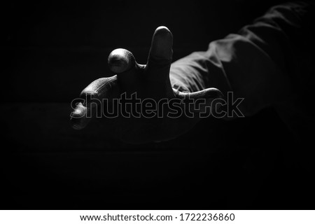 Front view of the scary hand of mysterious criminal in black glove reaching from the dark background in low key style, concept for mystery, crime,danger, threat and horror Royalty-Free Stock Photo #1722236860