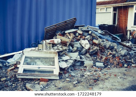 A pile of construction waste near private house. Building rubble, bricks, stones. Junk, garbage piled up near the building. Street scene. Recycling industry, rubbish removal and collection service #1722248179