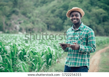 African farmer man holding tablet at organic farm with smile and happy.Agriculture or cultivation concept #1722256315