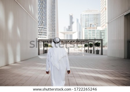 Emirates urban lifestyle in the big city with Arab guy investor checking out the city in gulf country. Photography of Arabian places and building construction.