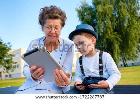 Caucasian grandmother and grandson in jeans suspenders, fedora hat with thoughtful face expression sitting on bench in park watching kid movie and cartoon on digital tablet pc. Concept of family day