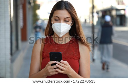 COVID-19 Pandemic Coronavirus Young Woman Wearing KN95 FFP2 Mask Using Smart Phone App in City Street to Aid Contact Tracing in Response to the 2019-20 Coronavirus Pandemic #1722270613