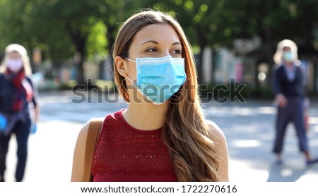 COVID-19 Social Distancing Woman in city street wearing surgical mask against disease virus SARS-CoV-2. Girl with face mask walks respecting social distancing during Pandemic Coronavirus Disease 2019. #1722270616