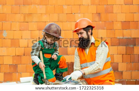 Family repairs during covid quarantine pandemic. Construction. Building a new house. Quality housing. Construction worker checking location site with wall on the background. Man and boy work. #1722325318