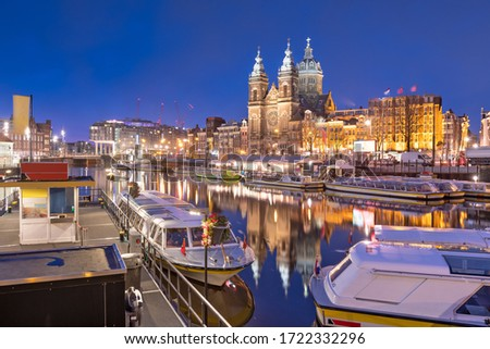 Amsterdam, Netherlands city center view with riverboats and the  Basilica of Saint Nicholas at night. #1722332296