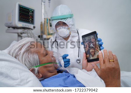Doctors and nurses are helping elderly corona virus/covid-19 infected patients in the ICU/ hospital, communicating to his family using tablet video call. #1722379042