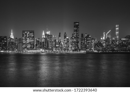 Black and White Monochromatic image of New York City Cityscape during Night Time with busy skyline and dense skyscrapers filling up the sky #1722393640