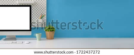 Close up view of creative workspace with blank screen computer, mug, tree pot and copy space on white table with shelf on light blue wall #1722437272