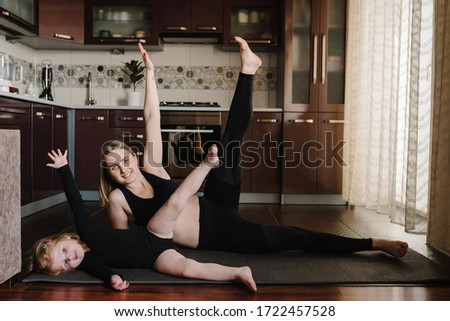 Mother and daughter are training at home. Happy family playing sports in the kitchen. Mom and kid are practicing yoga. Sports mom with child doing morning work-out, do the exercises together, healthy. #1722457528