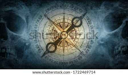 Skull of an old sailor pirate and vintage compass on a background of old paper. Symbol of travel, adventure, geographical discoveries, history, treasure hunt. Pirate and nautical grunge background. Royalty-Free Stock Photo #1722469714